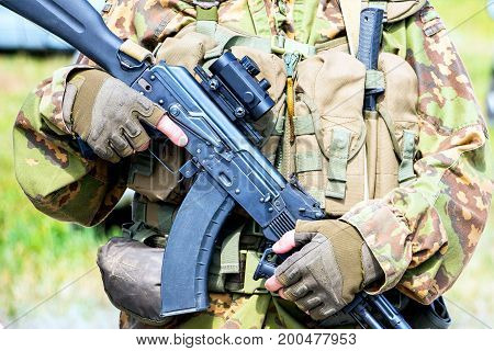 Soft focus. Soldier in camouflage holding a finger on the trigger of a Kalashnikov