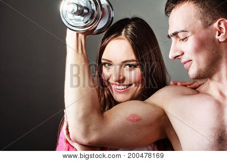 Bodybuilding. Strong man exercising with dumbbells. Closeup muscular guy flexing lifting weights girl looking admiringly kissing his biceps.