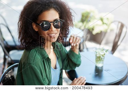 Portrait of young beautiful african girl in sungasses smiling resting relaxing in cafe on terrace. Copy space.