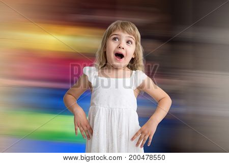 Funny kid in white dress jumping and laughing on colored background. Little pretty girl isolated on background. Sale, holidays, birthday party concept.