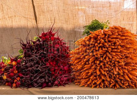 Organically grown beets and carrots are displayed and ready for sale at the local farmer's market.