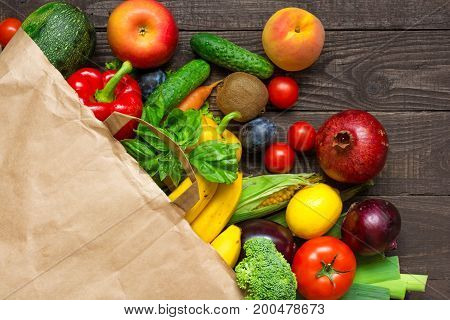 Full paper bag of different fruits and vegetables on rustic wooden background. healthy food. Top view. Flat lay