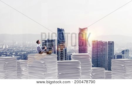 Thoughtful businessman sitting on pile of documents and looking away with cityscape and sunlight on background. Mixed media.