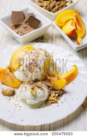 Ice cream with peach chocolate and nuts on white plate.