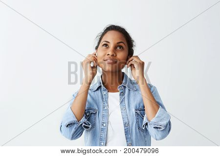 Dreamy looking Afro-american beautiful woman with black hair in blue shirt wearing earphones, listening to music, using music app on her smartphone.