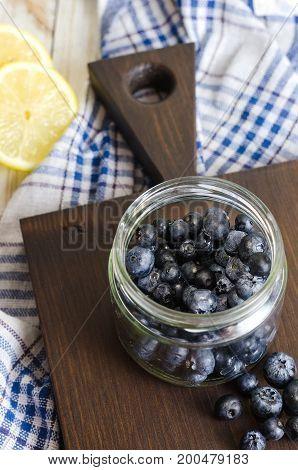 Blueberries antioxidant organic super food in a jar on wooden cutting board.