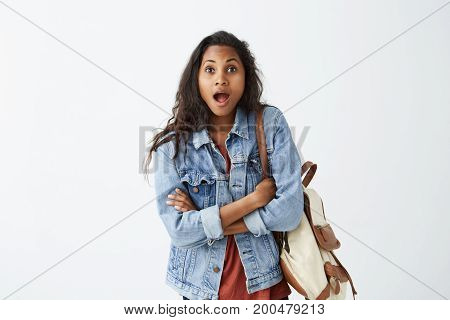Surprised Afro-American female student wearing denim jacket and red t-shirt with backpack looking at camera in shock, mouths wide opened and jaws dropped, keeping her arms folded, astonished with gossips about her friend.