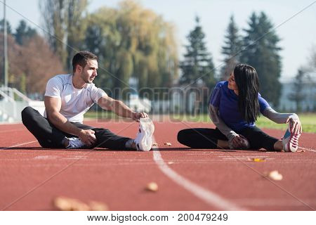 Couple Runner Stretching Leg In A City Park