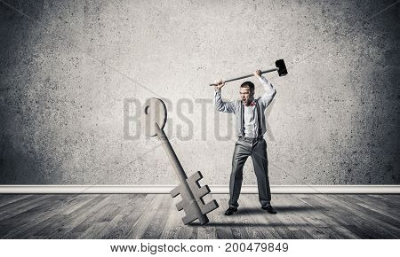 Determined businessman in concrete interior breaking with hammer stone key figure