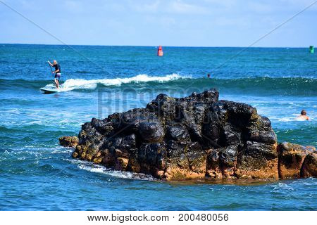 August 1, 2017 at Kalapaki Bay in Kauai, HI:  People surfing, swimming, and paddle boarding beside a small island of volcanic lava rocks taken at Kalapaki Bay where people can enjoy beachside activities on the Hawaiian coast taken in Kauai, HI
