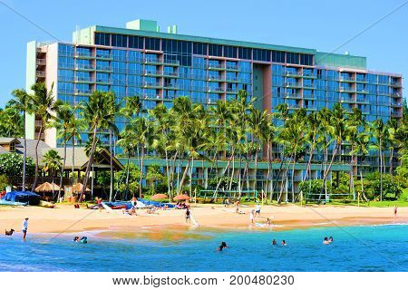 August 1, 2017 at Kalapaki Bay in Kauai, HI:  Sandy beach including Palm Trees and warm turquoise blue water with the Marriott Resort Lihue beyond where people can relax at the resort or sunbathe and swim at the beach taken in Kauai, HI