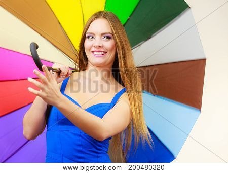 Woman fashion summer attractive girl wearing blue dress standing under colorful rainbow umbrella on gray. Positive smiling female model. Forecasting and weather season concept