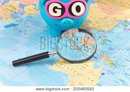 Going to Travel. Magnifier zoom spot on the map. Saving piggy bank with sunglasses and GO slogan staying on the world map.