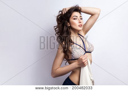 Very hot young model beckoned you. Sensual brunette passionately looking at the camera. Isolated on gray background. Studio shot