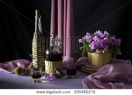 Still life with homemade liquor and wild cyclamen on a table close-up