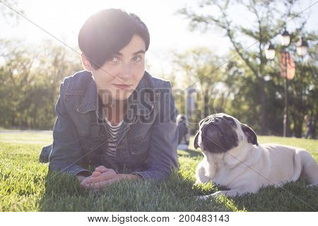 portrait of young woman and pug having god time in the park on green grass during sunset or sunrise