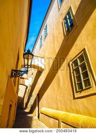 Morning Prague scene. Sunlit and long shadows on the wall with gas street lamp, Thunovska Street, Lesser Town, Prague, Czech Republic.
