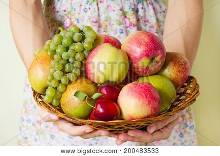 Fresh Ripe Fruit On A Wicker Wooden Plate In The Hands Of A Young Woman.  Autumn Harvest Of Fruits.
