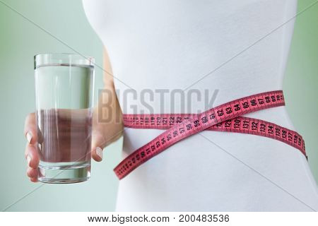 Slim woman in white underder holds a glass of water in her hand at the waist measuring tape. Concept of slimness
