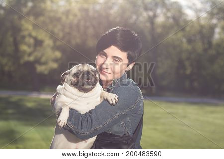 Young woman having good time with pug on the green grass, pretty girl with dog play in the park during sunset or sunrise