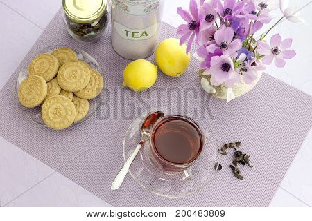 The tea in the cup, cookies, vase of flowers on a table close-up