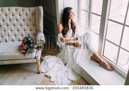 Woman By The Window. Bride Looking Out The Window, She Waits For The Groom. A Bridal Bouquet Lies On