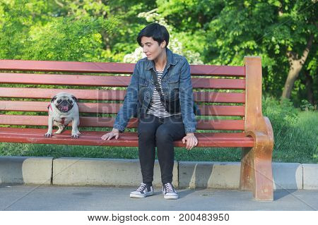 Portrait picture of young pretty woman in the park sit on bench, walk of female and pug in the summer park.