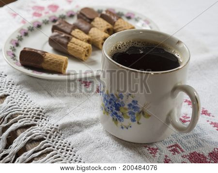 Old Chipped Cup With Black Coffee On Rustic Tablecloth With Plate With Chocholate Rolls
