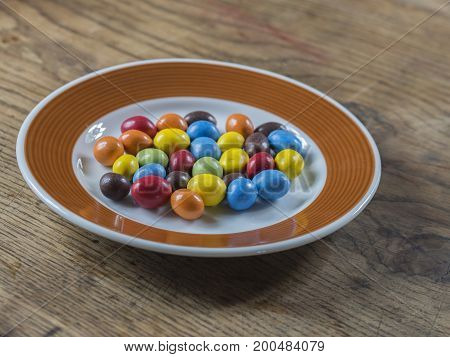 Colorful Bonbon Candy On White Brown Plate On Wooden Desk