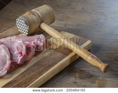 Fresh Raw Pork Chops  Meat With Old Meat Mallet On Chopping Board On Wooden Desk