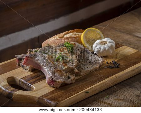 Fresh Made Grilled Pork Chop Steak With Green Herbs Bread Garlic Lemon Slice And Black Pepper On Thi