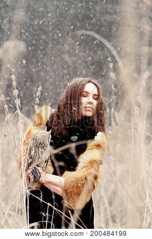 Woman in autumn in fur coat with owl on hand first snow. Beautiful brunette girl with long hair in nature holding an owl. Romantic delicate look girls