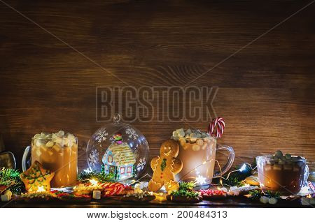 Dark wooden background with cocoa gingerbread cookies Christmas trees and gifts