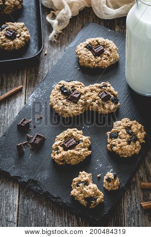 Homemade oatmeal raisin cookies with chocolate and milk on slate background. Selective focus, toned image