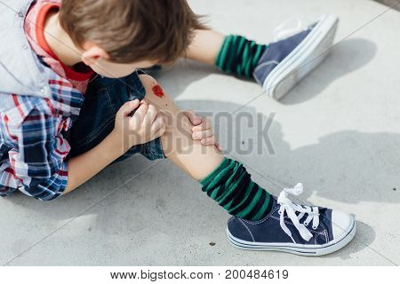 Injured boy sitting on concrete floor and looking at his scraped knee