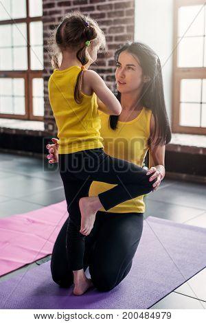 Kids yoga teacher teaching a girl child doing balance one-legged tree pose in gym.