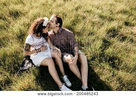Portrait of a loving pregnant couple sitting on grass. Happy expecting couple kissing in the nature.
