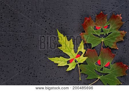 Halloween Decor - Autumn Maple Leaves With Evil Faces And Red Eyes. Black Background. Copy Space