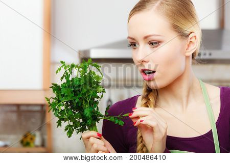 Woman In Kitchen Holds Green Aromatic Parsley