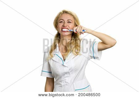 Young woman brushing teeth. Portrait of young beautiful nurse cleaning her teeth isolated on white background.