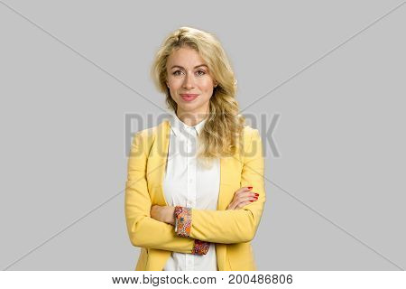 Beautiful business woman crossed arms. Attractive young european lady in fathion clothing crossed her arms standing on grey background.