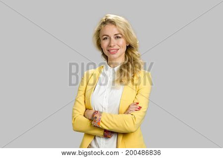Happy young office manager crossed arms. Successful business woman smiling isolated on grey studio with crossed arms.