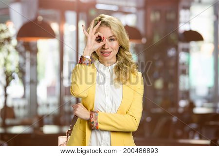 Attractive young woman gesturing ok. Beautiful business lady in yellow jacket and white shirt gesturing ok on blurred background.