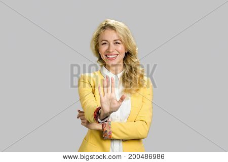 Smiling happy woman gesturing stop. Cheerful lady in yellow jacket making gesture stop while smiling on grey background. Facial expressions and body language.