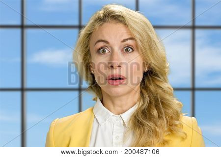 Portrait of surprised young woman. Beautiful blonde in yellow jacket looking surprised on blue sky window background close up.