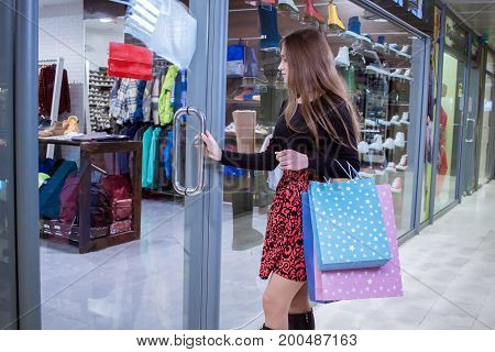 young woman with colorful bags enter the store