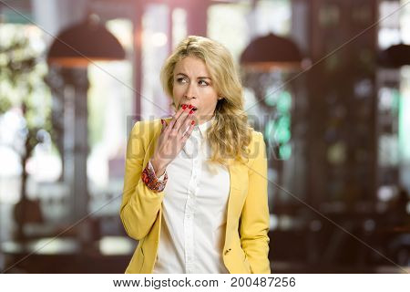 Young yawning woman looking away. Closeup portrait young blond woman placing hand covering mouth, yawning, looking away bored on blurred background.