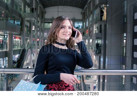 young lady in mall tolking with cellphone after shopping