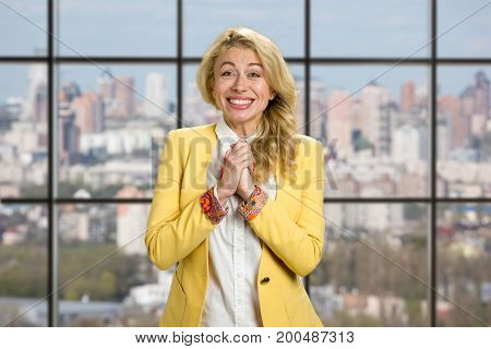 Portrait of excited happy business woman. Happy cheerful business woman clasped her hands in excitement on office window background.