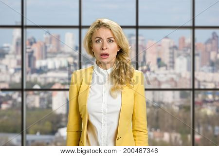 Shocked and stunned young woman. Young european business woman shocked and open her mouth on office window background.